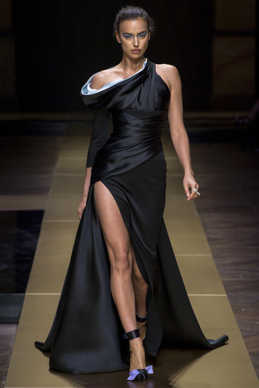 Модель в черном длинном платье с разрезом на показе Versace