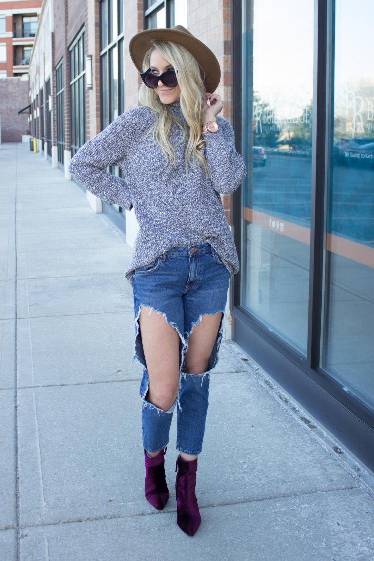 Девушка в рваных джинсах и свитере
