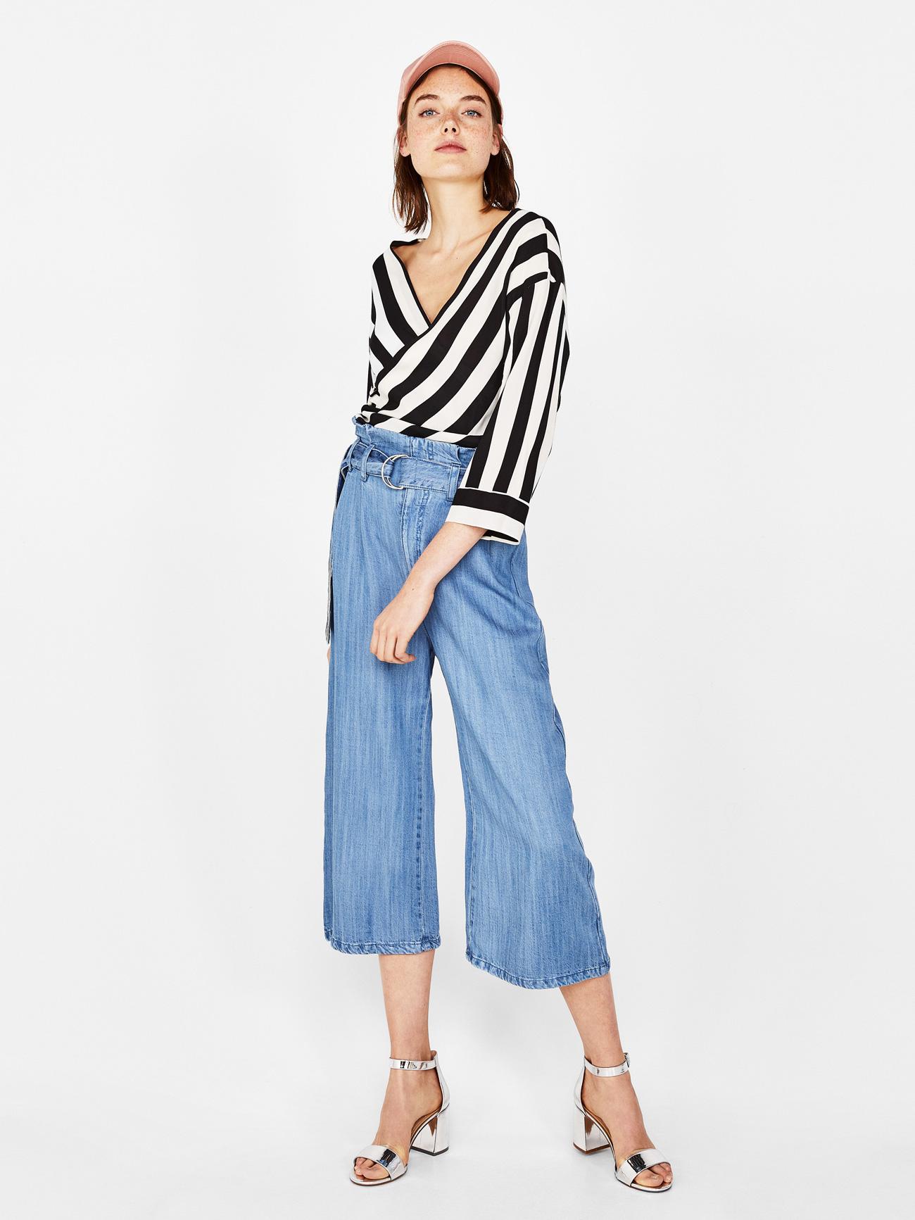 Модель в джинсовых кюлотах с завышенной талией